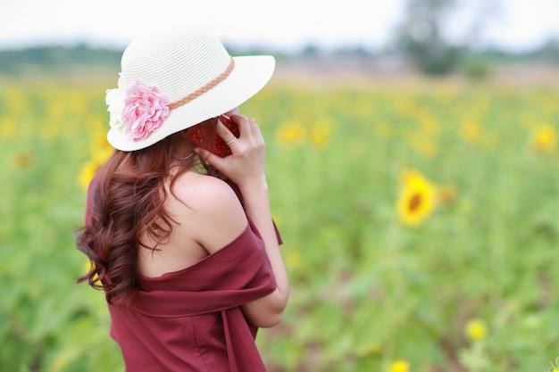 Piękna kobieta używa mądrze telefon podczas gdy na wakacje wakacje wśród kwiatu pola w naturze
