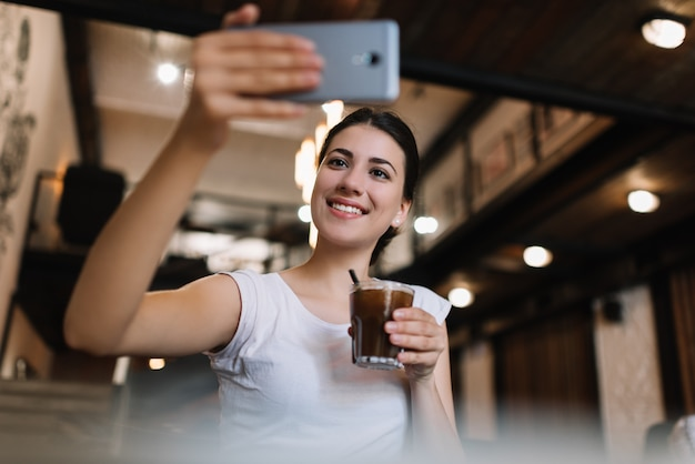 Piękna kobieta używa smartphone, bierze selfie, pije koktajl w kawiarni. uśmiechnięty bloger streaming wideo online