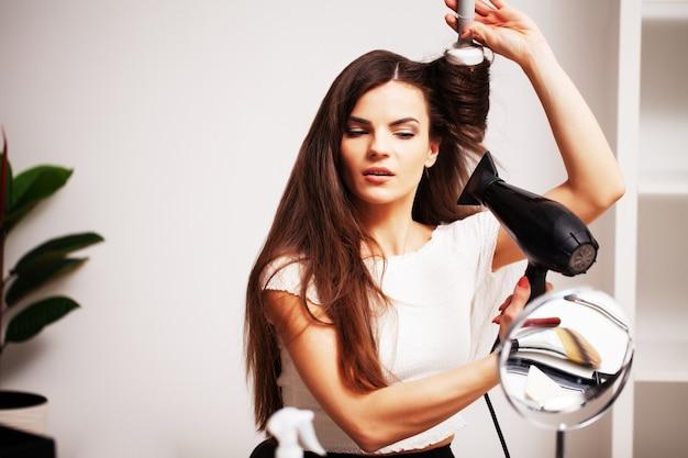 Piękna kobieta używa suszarki do włosów, aby wysuszyć włosy po kąpieli.