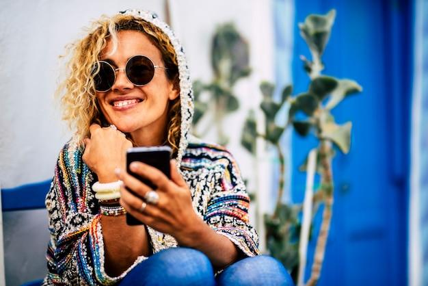 Piękna kobieta używa telefonu komórkowego i uśmiecha się