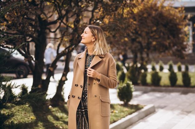 Piękna kobieta w beżowym płaszczu na zewnątrz w parku