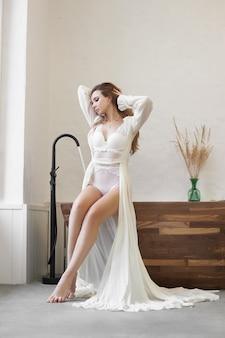 Piękna kobieta w białej bieliźnie i szlafroku w domu w łazience. zakochana kobieta odpoczywa
