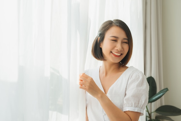 Piękna kobieta w białej jedwabnej szacie stojąca w pobliżu okna