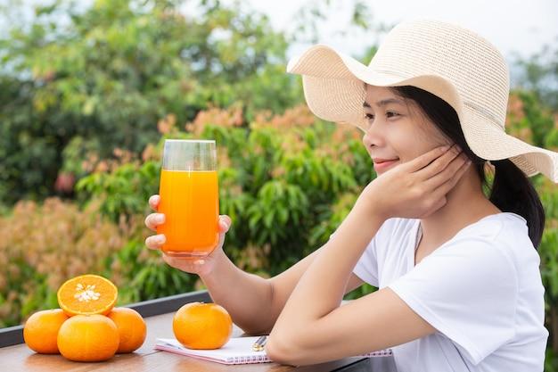 Piękna kobieta w białej koszulce z szklanką soku pomarańczowego