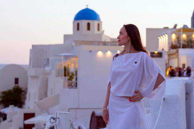 Piękna kobieta w białej sukni na tle architektury na santorini. zachód słońca.