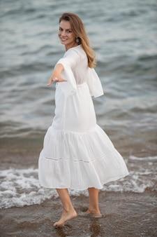 Piękna kobieta w białej sukni nad morzem