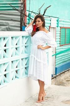 Piękna kobieta w białej sukni pozuje blisko turkusowego ogrodzenia