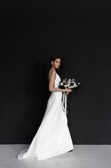 Piękna kobieta w białej sukni ślubnej na czarnym tle nowoczesna modna panna młoda w eleganckiej