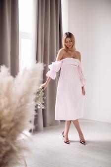 Piękna kobieta w białej sukni stojąca przy dużym oknie z dużą ilością blasku