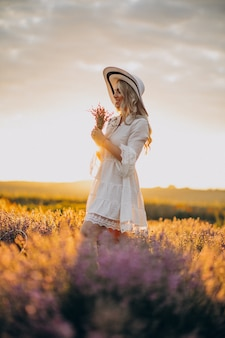 Piękna kobieta w białej sukni w polu lawendy