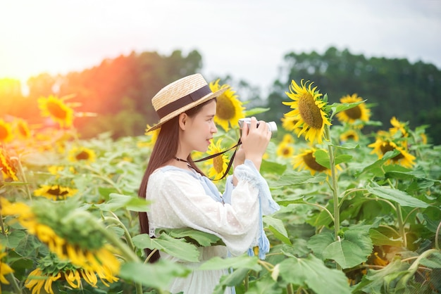 Piękna kobieta w białej sukni w słonecznikowym polu