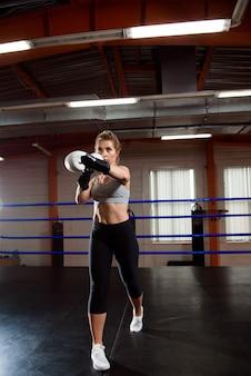 Piękna kobieta w białych rękawicach bokserskich w ringu na treningu.