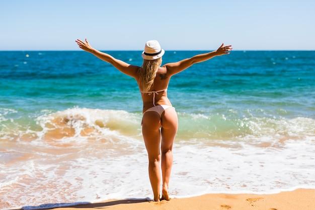 Piękna kobieta w białym bikini. młoda i sportowa dziewczyna pozuje na plaży latem