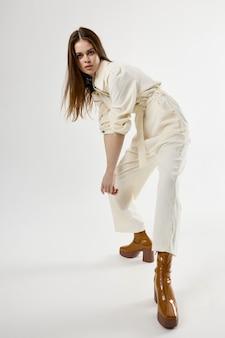 Piękna kobieta w białym garniturze brązowe buty moda na białym tle