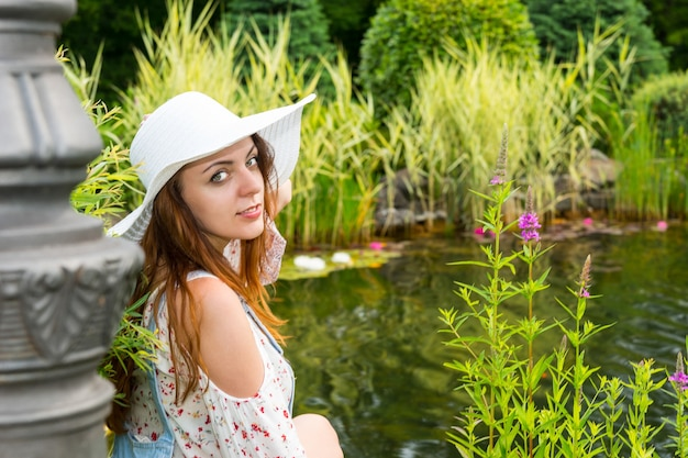 Piękna kobieta w białym kapeluszu siedząca nad jeziorem z różnymi roślinami, kwiatami w parku