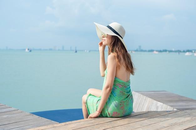 Piękna kobieta w białym kapeluszu siedzi na hotelu z plażą