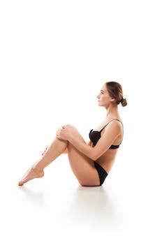 Piękna kobieta w bieliźnie na białej ścianie. koncepcja uroda, kosmetyki, spa, depilacja, leczenie i fitness. wysportowane i wysportowane, zmysłowe ciało o zadbanej skórze, wykonujące ćwiczenia.
