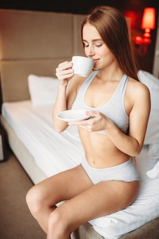 Piękna kobieta w bieliźnie pije kawę w łóżku, dzień dobry. dziewczyna budzi się w sypialni