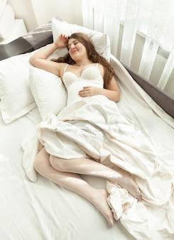 Piękna kobieta w bieliźnie śpi w łóżku przed oknem