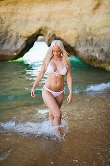 Piękna kobieta w bikini. młoda i sportowa dziewczyna pozuje na plaży latem