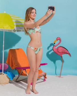 Piękna kobieta w bikini robi selfie