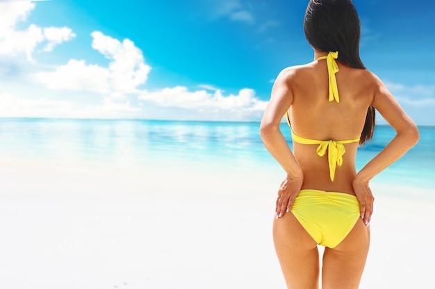 Piękna kobieta w bikini stojąc z rękami uniesionymi do bioder, ciesząc się, patrząc widok na ocean w upalny letni dzień