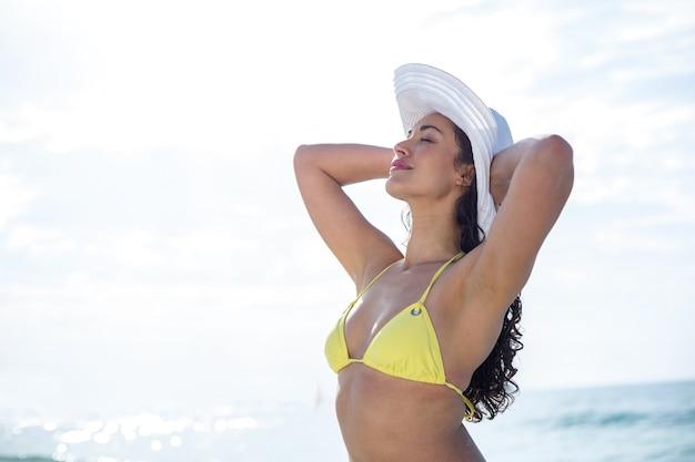 Piękna kobieta w bikini stojąc z rękami za głową