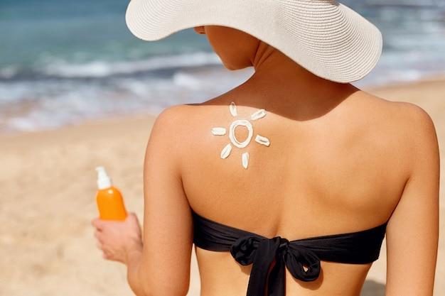 Piękna kobieta w bikini stosując krem do opalania na opalonym ramieniu.