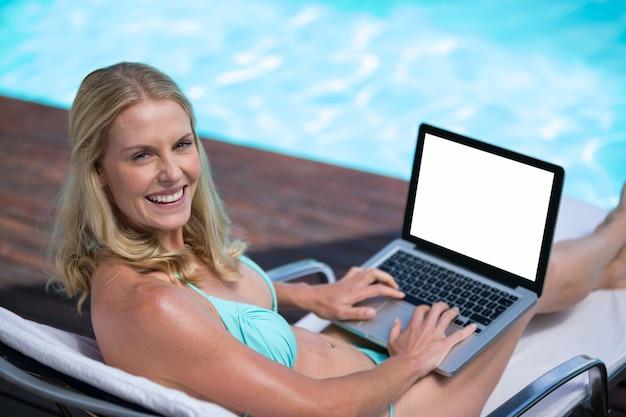 Piękna kobieta w bikini za pomocą laptopa w pobliżu basenu
