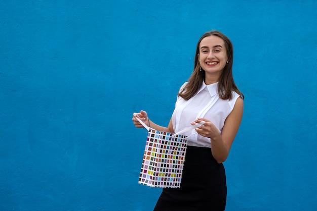 Piękna kobieta w biznesie tkaniny trzymając torby na zakupy na białym tle