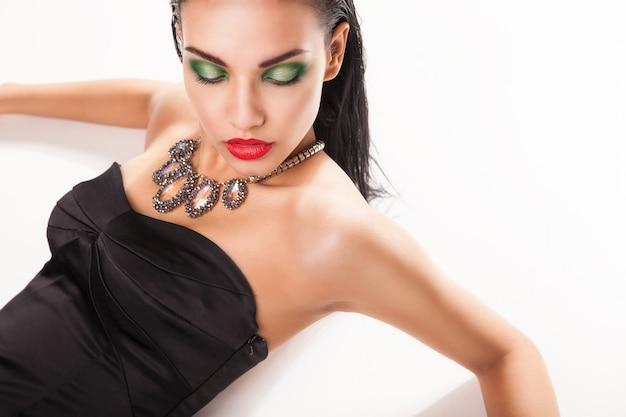 Piękna kobieta w biżuterii leżąca na białym