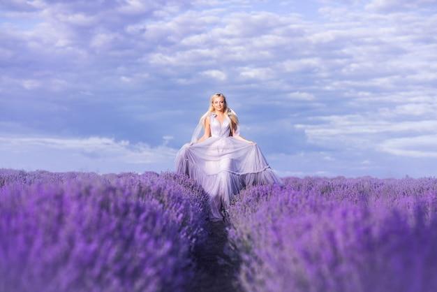 Piękna kobieta w bujnej długiej sukni biegnie w lawendowym polu. dziewczyna na obrazie wróżki i księżniczki kwiatów.