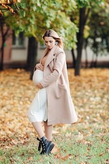 Piękna kobieta w ciąży cieszy się ciążą w parku