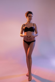Piękna kobieta w ciąży dotyka jej brzucha i patrząc na bok w studio z kolorowym światłem