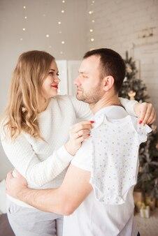 Piękna kobieta w ciąży i jej przystojny mąż trzymają body niemowlęce i uśmiechając się