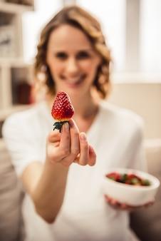 Piękna kobieta w ciąży je truskawki.