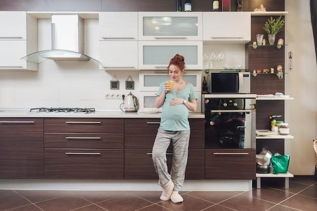 Piękna kobieta w ciąży relaks w domu ze szklanką soku