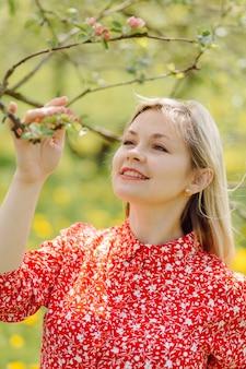 Piękna kobieta w ciąży relaks w parku na sobie czerwoną sukienkę