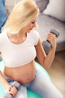 Piękna kobieta w ciąży robi ćwiczenia za pomocą hantle