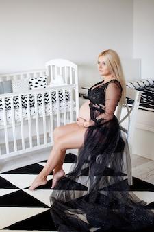 Piękna kobieta w ciąży siedzi w czarno-białym pokoju w domu