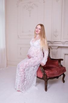 Piękna kobieta w ciąży siedzi w fotelu