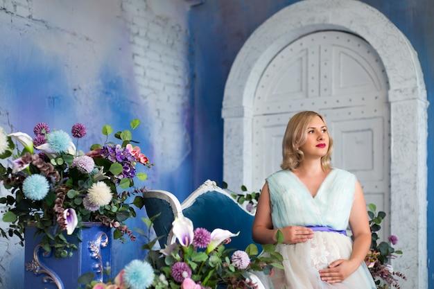 Piękna kobieta w ciąży siedzi wśród kwiatów na zdjęciu na niebieskiej ścianie w stylu loftu
