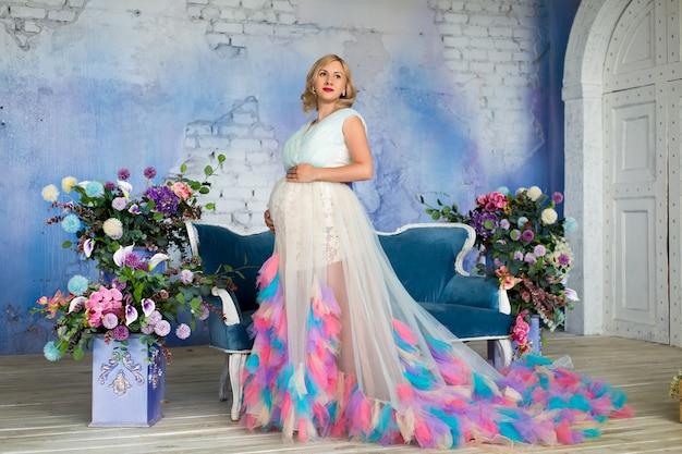 Piękna kobieta w ciąży stoi w bujnej kwiecistej sukni na strychu wśród kwiatów na niebieskiej ścianie