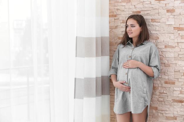 Piękna kobieta w ciąży stojąca w pobliżu okna w domu