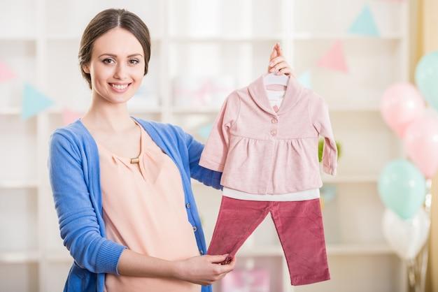 Piękna kobieta w ciąży trzyma ubrania dla dzieci.