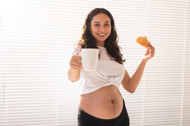 Piękna kobieta w ciąży, trzymając w rękach rogalika i filiżankę kawy podczas porannego śniadania