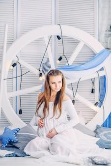 Piękna kobieta w ciąży w białej sukni siedzi między stylowymi poduszkami na tle dużego białego koła z żarówkami i drewnianymi ekranami i trzyma ciężarny brzuch