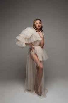 Piękna kobieta w ciąży w długiej modnej sukience, obraz na białym tle na szarym tle