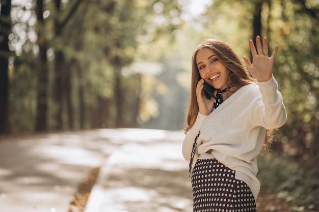 Piękna kobieta w ciąży w jesiennym parku