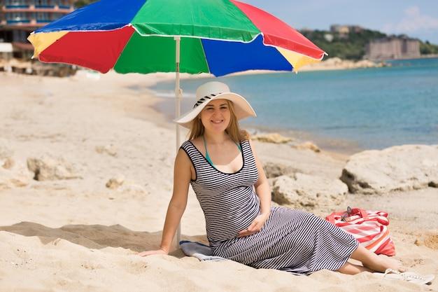 Piękna kobieta w ciąży w paski sukienka i biały kapelusz relaks na plaży w słoneczny dzień